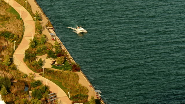 motor boat passing riverside on detroit river. view from above - detroit river stock-videos und b-roll-filmmaterial