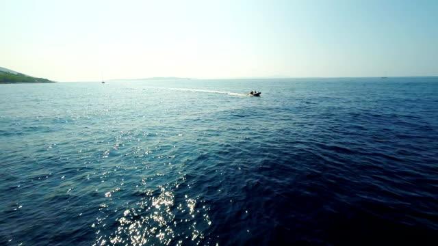 vídeos y material grabado en eventos de stock de aérea de motor boat sailing contra el sol - multicóptero