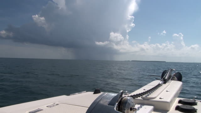 a motor boat sails in the florida keys as a thunderstorm hovers over the waters nearby - scott mcpartland bildbanksvideor och videomaterial från bakom kulisserna