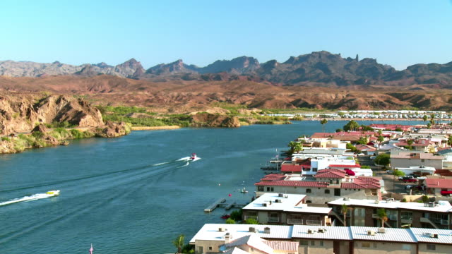 WS ZO Motor boats on Colorado River and roof tops of Cienega Springs with red rock mountain range in distance, Cienega Springs , Arizona