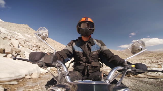 Motor cyclist negotiates rough Himalayan road
