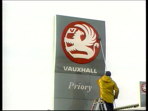 British motorists still overcharged for their motors LIB Vauxhall sign being washed LBV Man cleaning sign Car driven from production line in car...