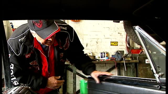 general motors halts production of pontiac; england: london: robin gray showing reporter his gto, pontiac gto in garage and interview sot - ポンティアック点の映像素材/bロール