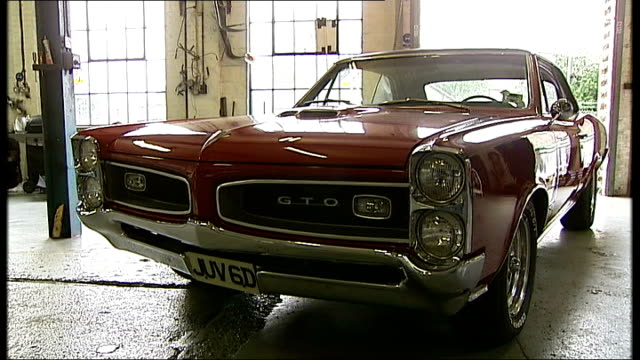 general motors halts production of pontiac; int/ext pontiac gto car in garage and trans am car outside - ポンティアック点の映像素材/bロール