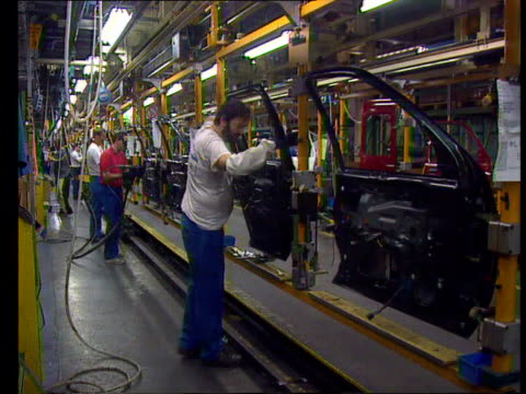 Rover/Ford LIB Essex Dagenham INT Workers working on cars doors as along on production line at Ford car plant Worker fitting window to rear door of...
