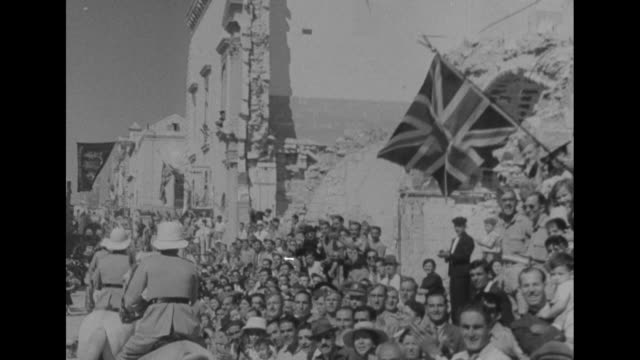 motor launches in malta harbor / george vi greets 6th viscount gort john vereker at dock / pov ride through street past union jack with damaged... - barca a motore video stock e b–roll