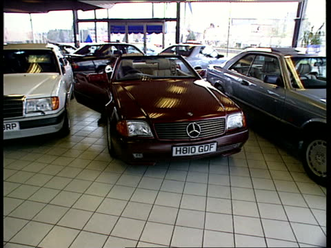 vídeos y material grabado en eventos de stock de motor manufacturrers to be forced to pay to scrap cars locations unknown mercedes cars on display in showroom as customer gets into one tgv mercedes... - sala de muestras