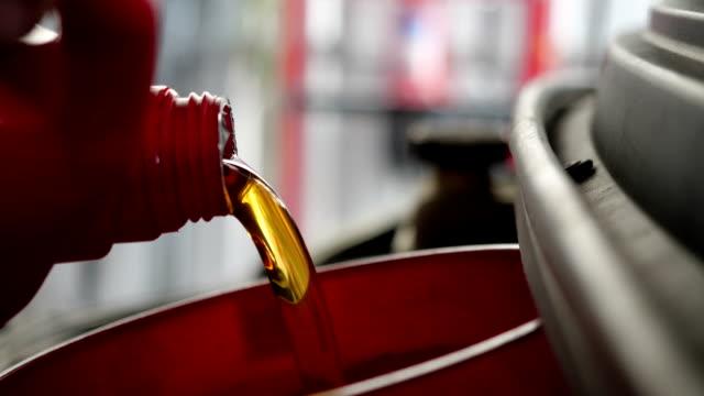 vídeos de stock, filmes e b-roll de óleo de motor derramando para o motor do carro. óleo fresco derramado durante uma troca de óleo para um carro. - motor