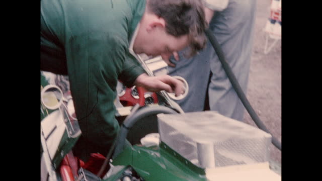 vídeos y material grabado en eventos de stock de motor racing action and scenes in the pit lane with drivers and mechanics working on vehicles being watched by enthusiasts during the international... - northamptonshire