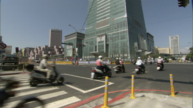 ws tu la motor scooters riding on street and taipei 101 skyscraper with traffic lights in foreground / taipei, taipei county, taiwan - taipei 101 stock videos & royalty-free footage