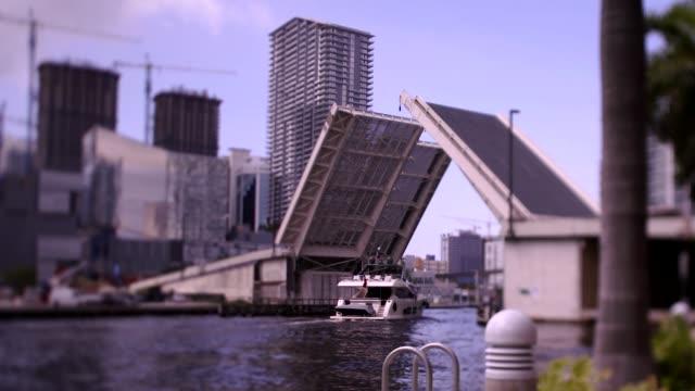motor yacht passing under a raised drawbridge on miami river in downtown district, miami, florida - drawbridge stock videos & royalty-free footage