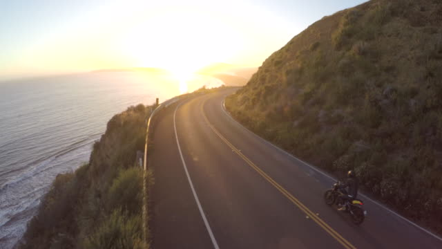 motorbike driving on a highway by the coast during a stunning sunset in california - coastline stock videos & royalty-free footage