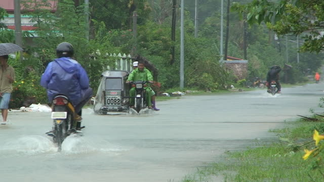 motorbike driving through flood waters 60km ne of laoag, philippines, typhoon parma 4th october 2009 - gale stock videos & royalty-free footage