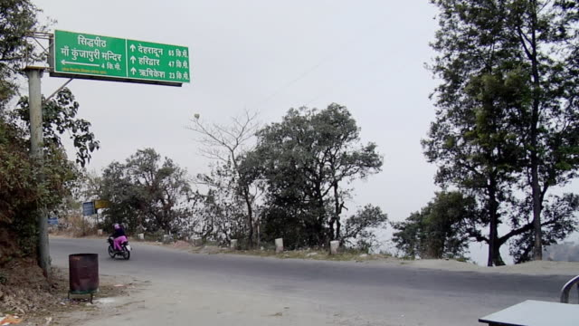 ws motorbike passing on road, signpost in foreground / rishikesh, uttarakhand, india - indian arrowhead stock videos and b-roll footage