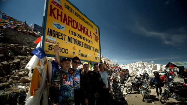 motorbike tourists celebrate reaching the khardungla pass, the highest passable road in the world - mountain pose stock videos and b-roll footage