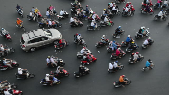 motorbike traffic at crowded junction in ho chi minh city (saigon), vietnam. - chaos stock-videos und b-roll-filmmaterial