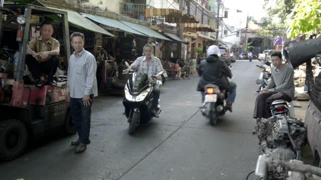 vidéos et rushes de motorbikes drive in the street of scrap dealers - hommes d'âge moyen