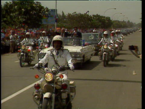 motorbikes flank cars in motorcade king sihanouk stands waving to crowds in first car celebrating his return to cambodia after 13 years in exile... - 追放点の映像素材/bロール