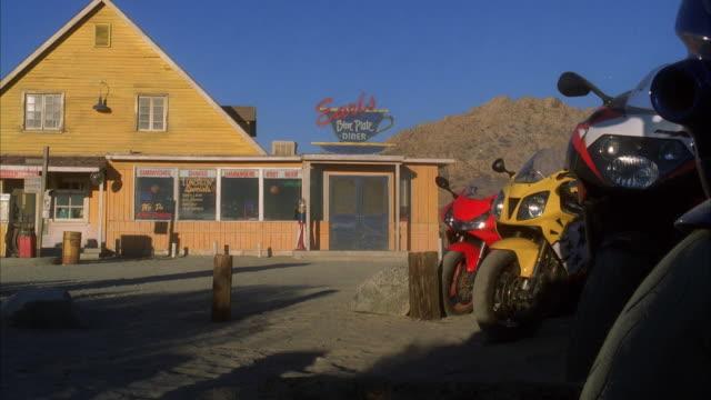 vídeos de stock, filmes e b-roll de ws motorbikes parked in front of diner - escrita ocidental