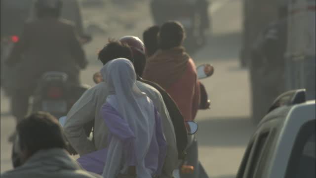 vídeos de stock, filmes e b-roll de motorbikes travel along busy road, rishikesh available in hd. - rishikesh