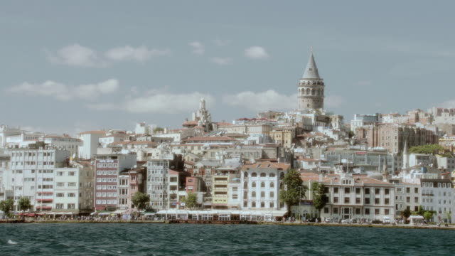 pov motorboat cruising past the bosphorus coastline crowded with buildings / istanbul, turkey - vagare senza meta video stock e b–roll