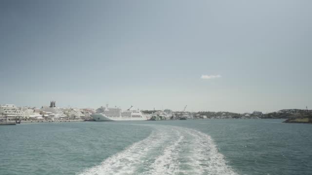 Motorboat departs from Hamilton, Bermuda Island, cruise ship in backround
