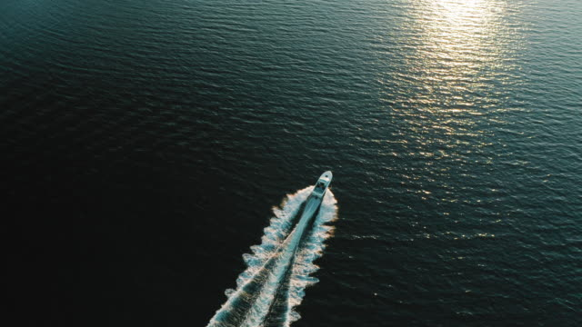 motorboat moving towards the sunset - aerial view - motorboat stock videos & royalty-free footage
