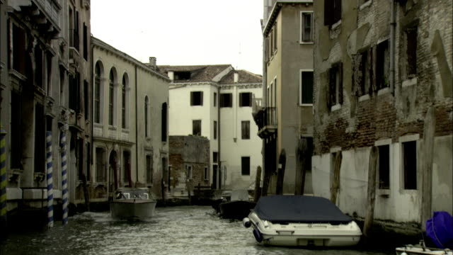 a motorboat passes docked gondolas along a venetian canal. available in hd. - ghetto video stock e b–roll