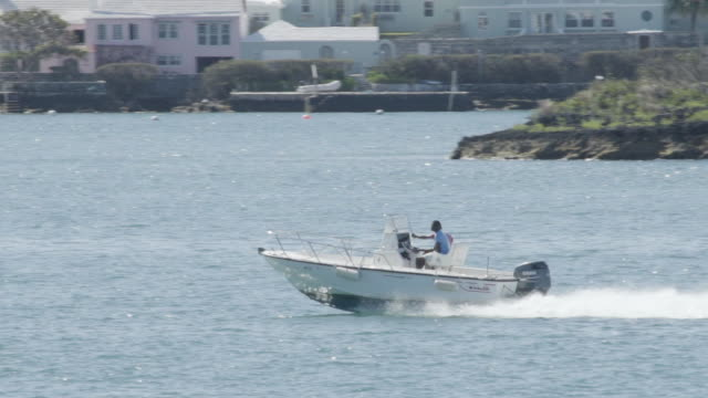 motorboat passing the costline of hamilton, bermuda island, in slow motion - motorboat stock videos and b-roll footage
