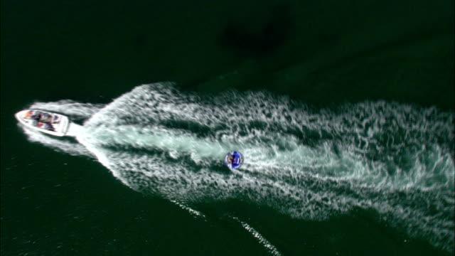 vídeos y material grabado en eventos de stock de a motorboat pulling a raft cruises along a coastline with cliffs. available in hd. - pasear en coche sin destino