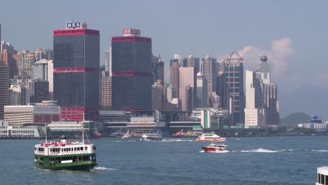 motorboat sails across victoria harbor, a barge sails past a star ferry vessel on victoria harbor as viewed from the tsim sha tsui district of hong... - star ferry stock-videos und b-roll-filmmaterial