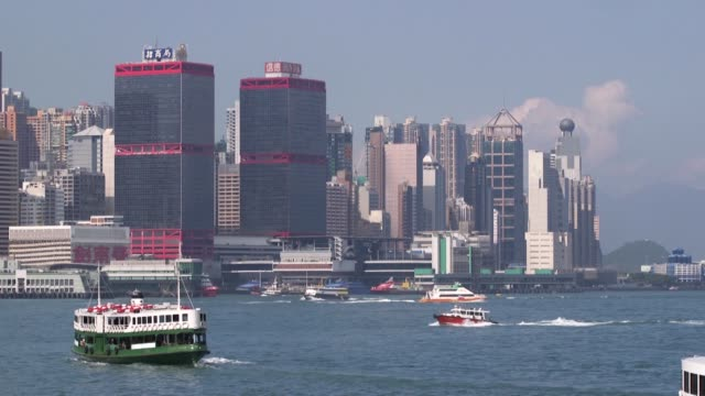 a motorboat sails across victoria harbor a barge sails past a star ferry vessel on victoria harbor as viewed from the tsim sha tsui district of hong... - star ferry bildbanksvideor och videomaterial från bakom kulisserna