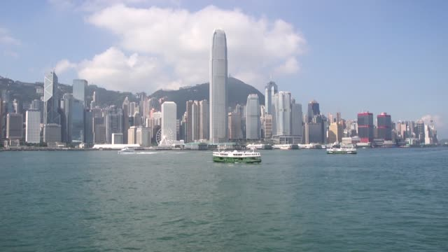 motorboat sails across victoria harbor, a barge sails past a star ferry vessel on victoria harbor as viewed from the tsim sha tsui district of hong... - star ferry bildbanksvideor och videomaterial från bakom kulisserna