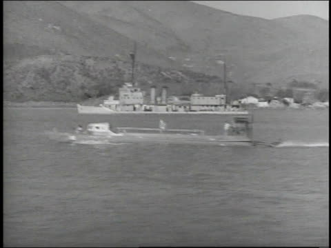 stockvideo's en b-roll-footage met 1938 ws motorboat speeding by other ships on water with mountains in background / japan - 1938