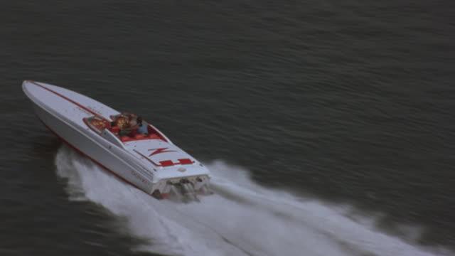 a motorboat speeds through a harbor. - motoscafo da competizione video stock e b–roll