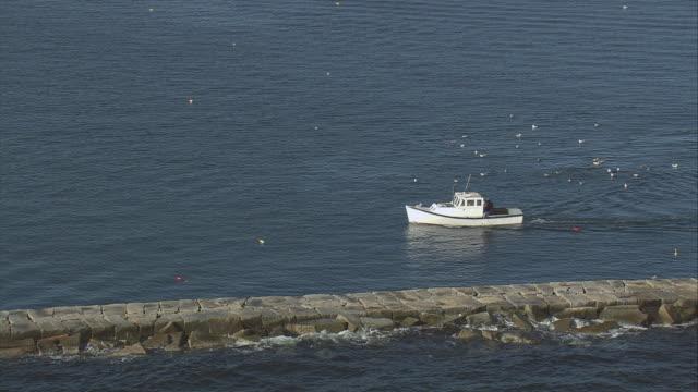 vídeos de stock, filmes e b-roll de aerial motorboat traveling slowly past a seawall / rockland, maine, united states - quebra mar