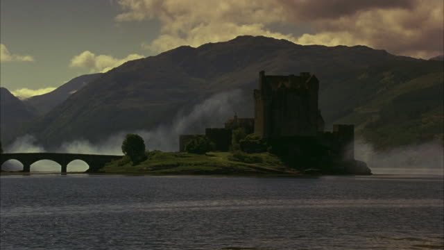 a motorcade drives over a bridge leading to the eilean donan castle in scotland. - schottisches hochland stock-videos und b-roll-filmmaterial