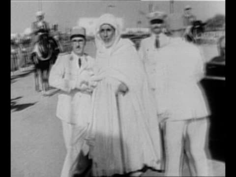 motorcade escorts sultan mohamed ben arafa's vehicle along street as soldiers with bayoneted rifles line it on both sides / ls row of mounted black... - sultan stock videos and b-roll footage