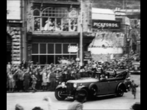 motorcade led by car bearing winston churchill and his wife clementine approaches on street lined with waving crowds / spectators look down from atop... - winston churchill stock videos & royalty-free footage