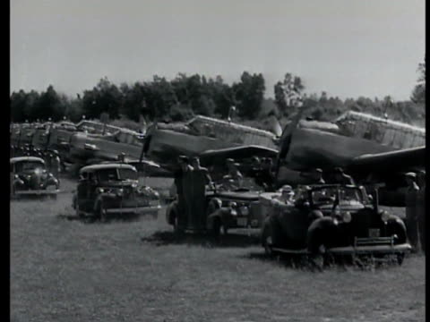 Motorcade moving beside airfield airplanes MS US President Roosevelt Canadian Prime Minister Mackenzie Secretary of State Henry Stimson in backseat...