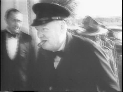 Motorcade of car and motorcycles pulls up to armory / Winston Churchill walks up to the door of a building with a cigar in his mouth / closeup of...