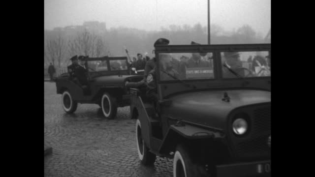 VS motorcade of open jeeps carrying members of different countries' military enters United Nations Palais de Chaillot parade grounds pass French...