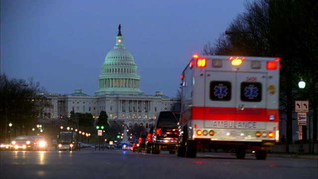 stockvideo's en b-roll-footage met a motorcade of secret service and emergency vehicles drives with flashing lights toward the u.s. capitol in washington, d.c. - bewakingspersoneel