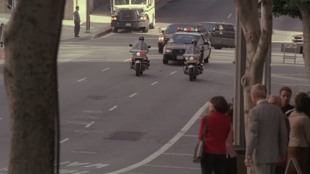stockvideo's en b-roll-footage met pan motorcade passing pedestrians and turning to drive between buildings and past watching secret service agent / washington, d.c., united states - geheime dienstagent