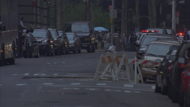 a motorcade speeding past parked cars and pedestrians in manhattan. - motorcade stock videos & royalty-free footage