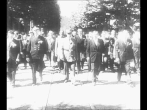 vidéos et rushes de motorcade with motorcycle escort approaches with marshal philippe petain leader of vichy france standing in lead car crowds line street at left /... - officier grade militaire