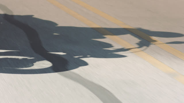 vidéos et rushes de slo mo. motorcycle casts shadow on yellow lines of highway. - moto