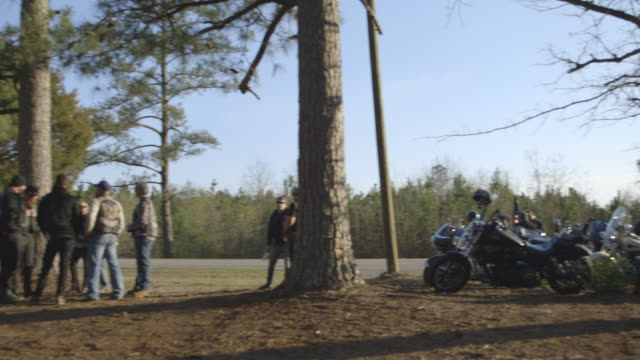 motorcycle club members talk by side of the road - bande stock-videos und b-roll-filmmaterial