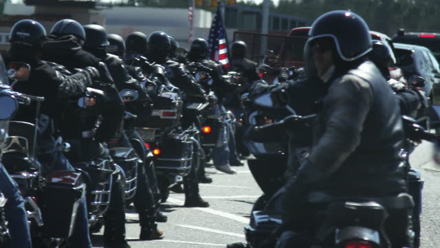 motorcycle club sits in traffic, pan right, close up - bande stock-videos und b-roll-filmmaterial