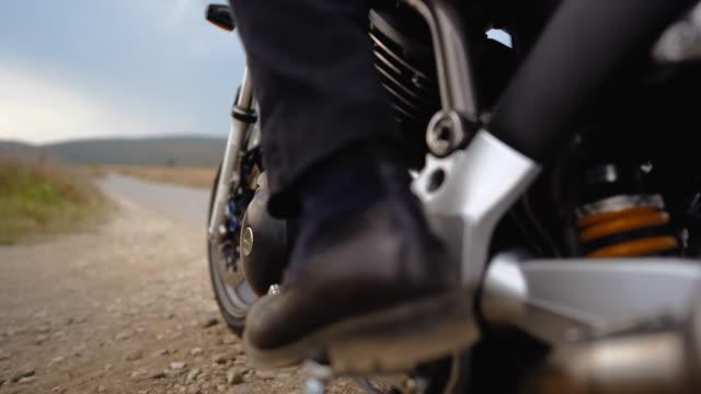 vídeos de stock, filmes e b-roll de motociclista colocando capacete e iniciando uma moto - capacete esportivo